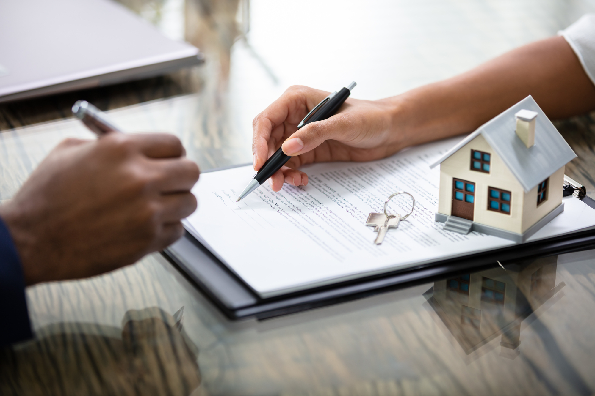 Businessman Signing Real Estate Contract With Keys On It