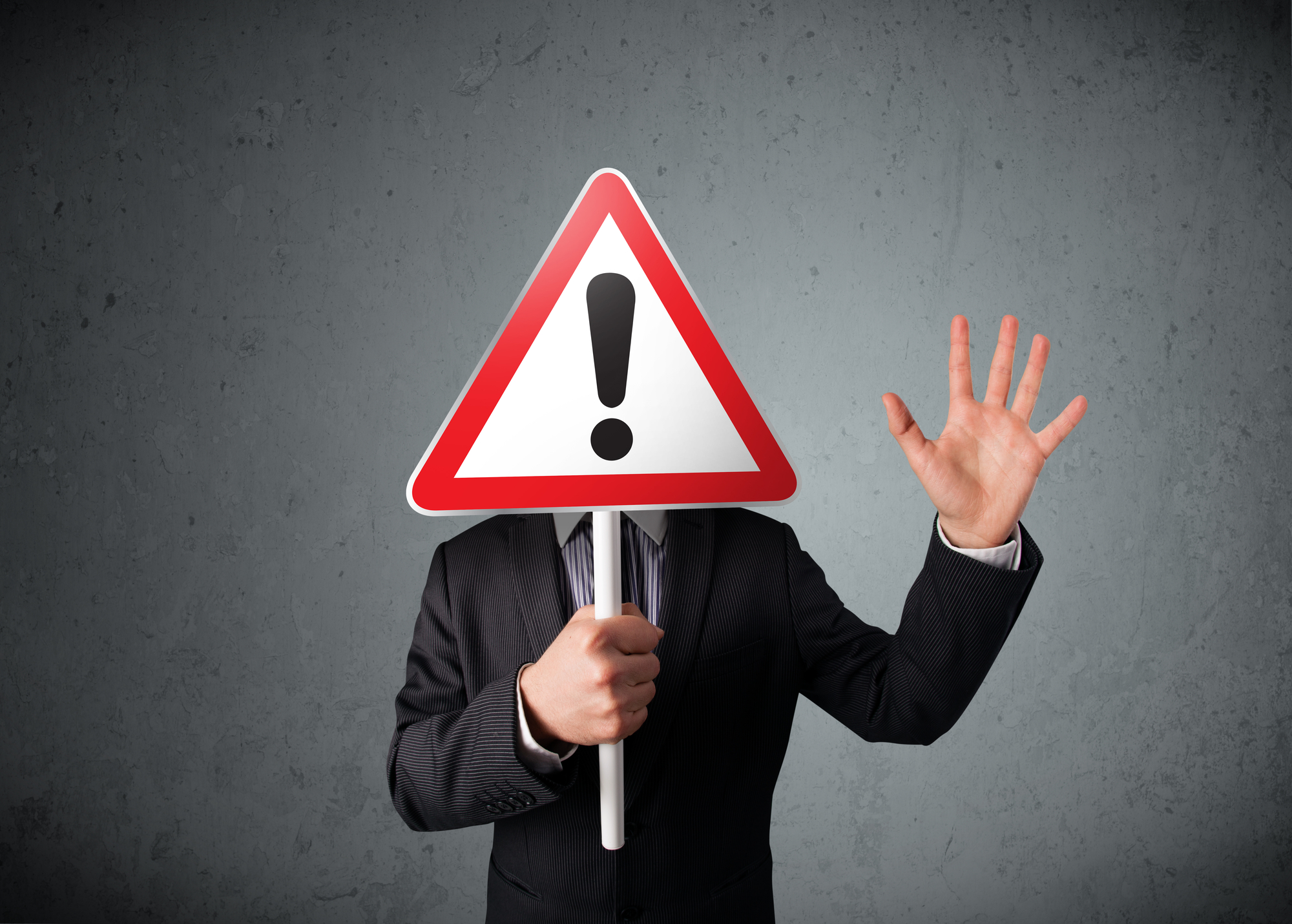 Businessman holding an exclamation road sign
