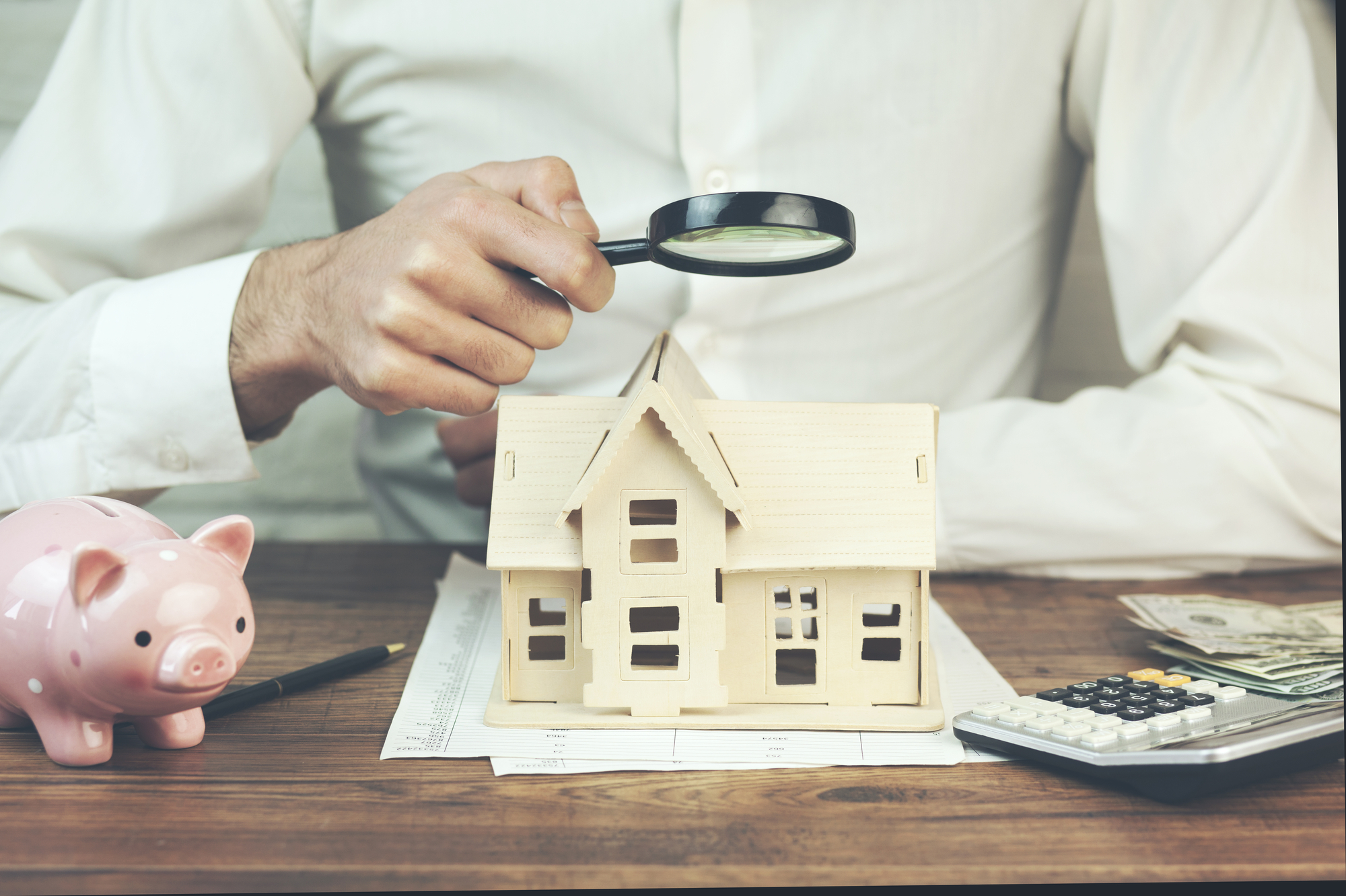 Businessman holding magnifier with house model and piggy bank