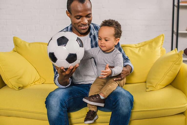 Happy young father holding soccer ball while sitting with adorable little son on sofa (R) (S)