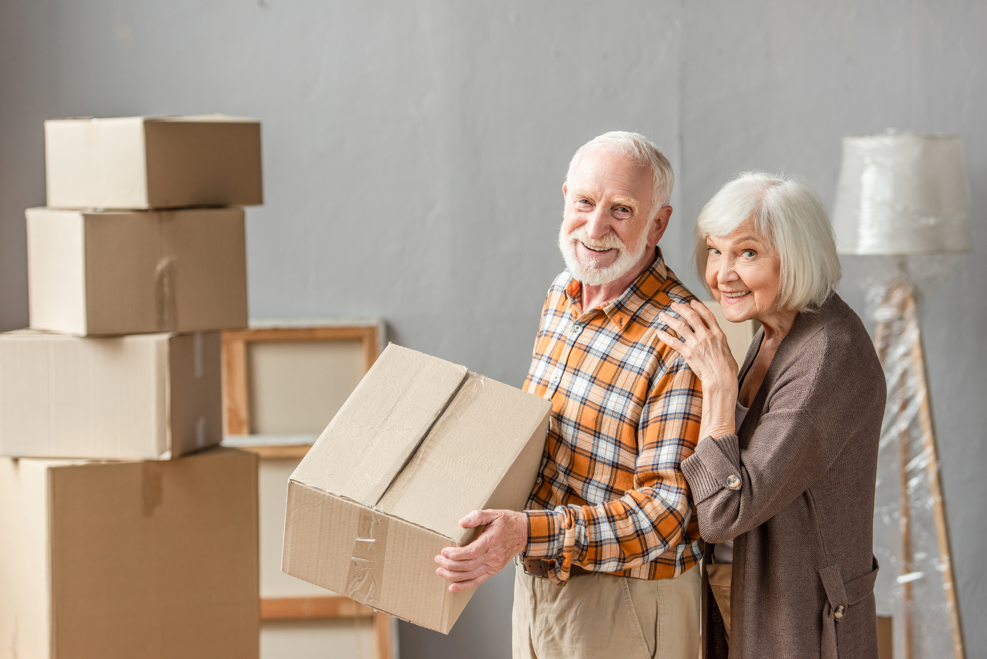 Senior man holding cardboard box and wife leaning on shoulder in new house, moving concept