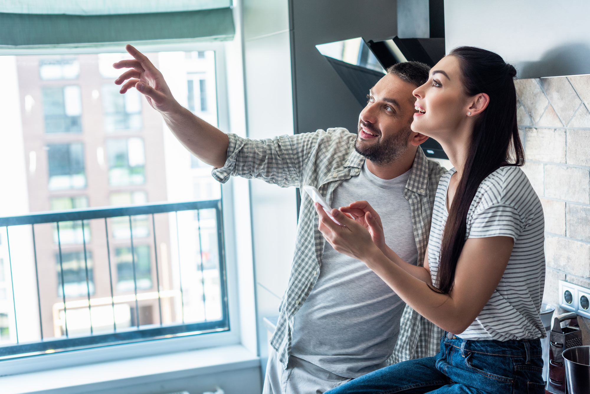 Side view of smiling couple with smartphone looking away together in kitchen, smart home