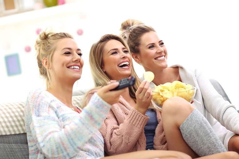 Three beautiful young women watching tv at home (R) (S)