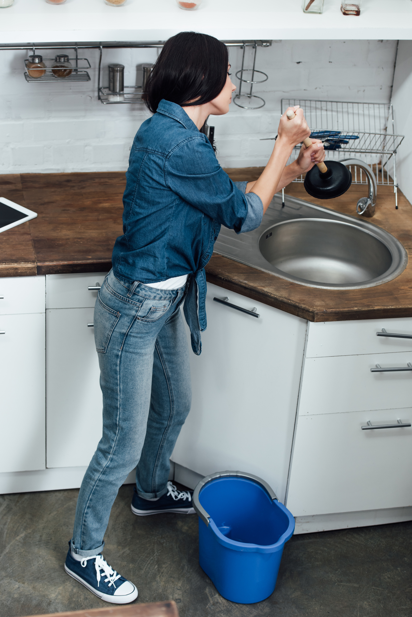 Woman in blue jeans using plunger in kitchen