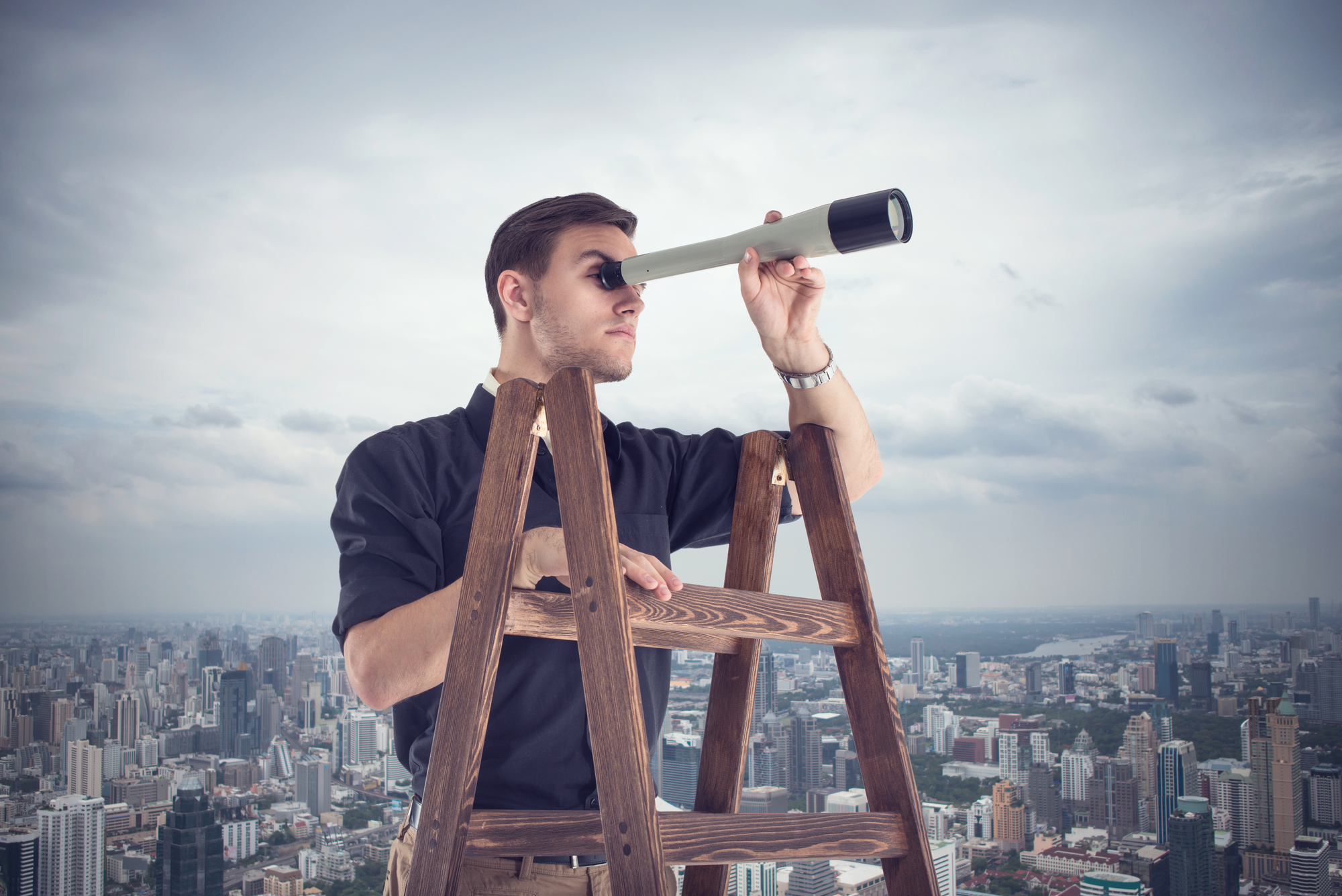 Young businessman looking for future opportunities through the spyglass standing on stairs