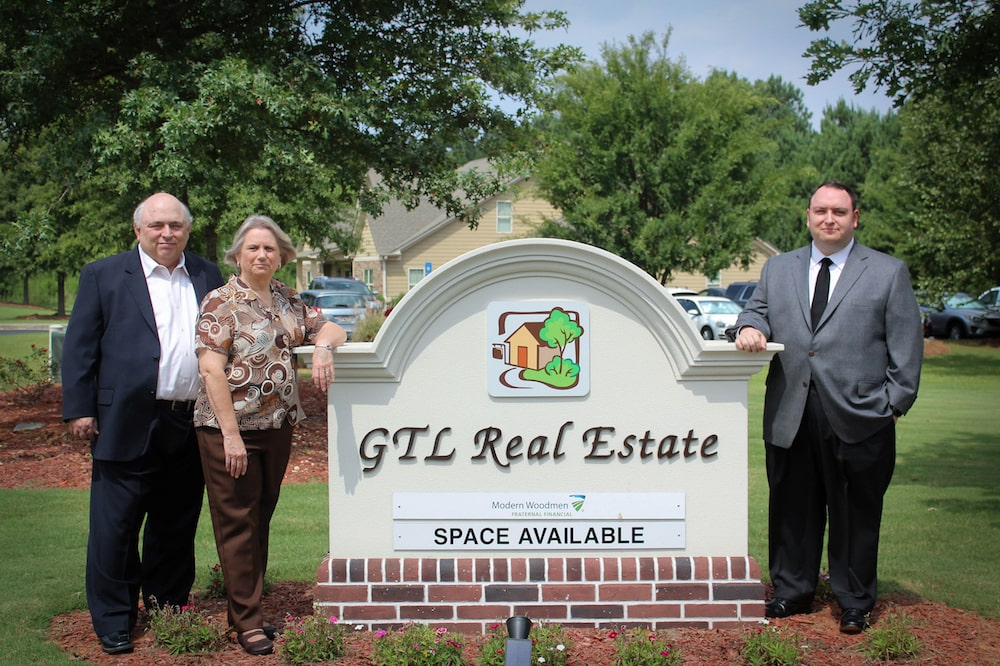 Gary, Lana, and Todd Ortscheid posing with the GTL Real Estate sign in front of the office. GTL Real Estate provides property management and investment services in Atlanta and the surrounding areas