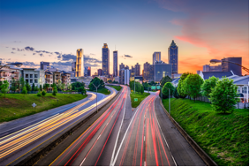 A busy highway below the city skyline where GTL Real Estate provides Atlanta property management for local rental properties.