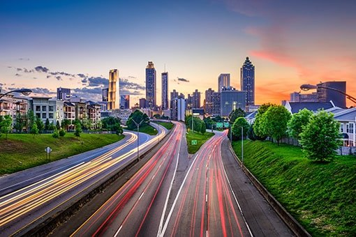 A busy highway below the city skyline at sunset, near where GTL Real Estate can provide Roswell property management for your investment.